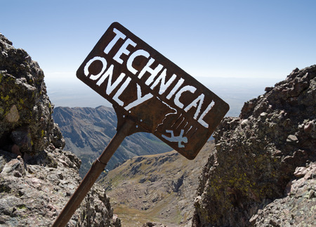 steep cliff sign: technical only sign with falling climber above a steep cliff on Crestone Needle Peak Stock Photo