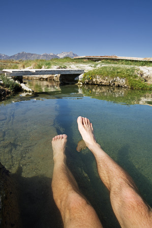 a mans legs soaking in a hot spring in the Eastern Sierra of California photo