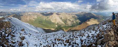 outdoorsman: a man on the top of Mount Elbert the highest peak in Colorado with a sweeping summit panorama