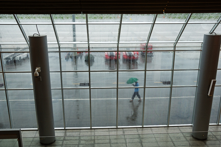 looking out through an airport window on a rainy day with a person walking by outside with umbrella