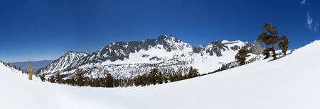 panorama of Onion Valley covered in snow with University Peak and blue sky Stock Photo