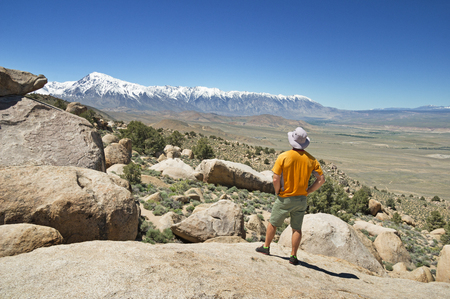 the back of a man looking at the Sierra Nevada Mountains from an overlook at the Druid Stones near Bishop California Stock Photo