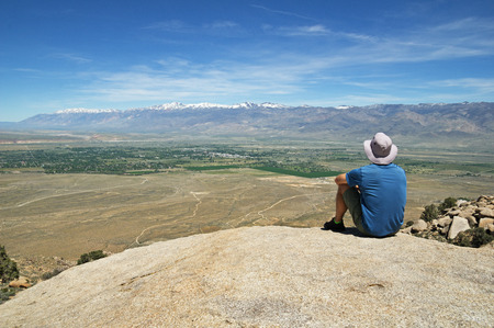 a man with a hat facing away sits on a rock overlook looking down at the Owens Valley and the town of Bishop
