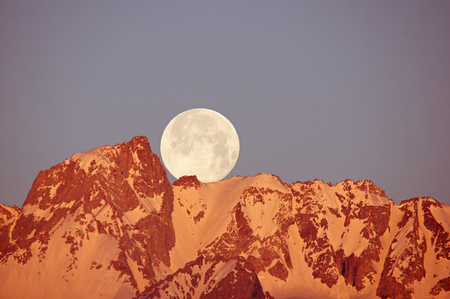 mount humphreys: a full moon setting over Mount Humphreys mountain as the first light hits the summit