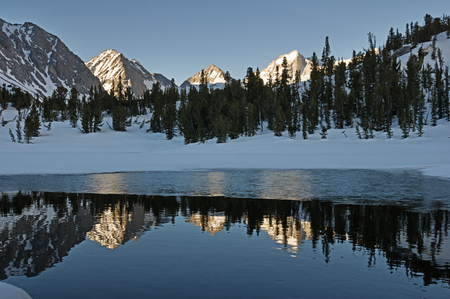 mountains reflected in a pool in a snowy pond in the Eastern Sierra Range