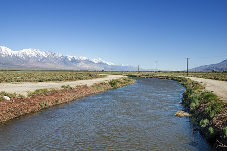 Los Angeles aqueduct in the Owens Valley with snowy Sierra Nevada mountains Stock Photo