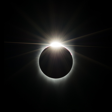 the sun begins to show from behind the moon in a solar eclipse creating a diamond ring