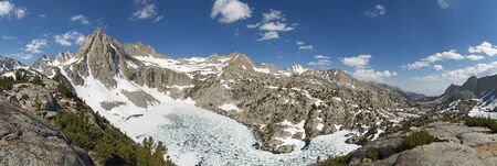 Picture Peak and partly frozen Hungry Packer Lake in July with a lot of snow in the Sierra Nevada Mountains of California