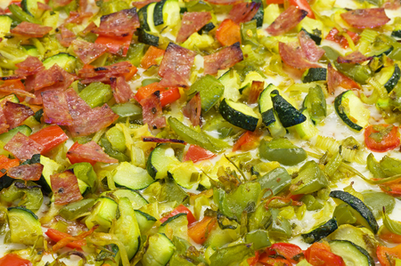 angled background view of a pizza top with vegetables and salami