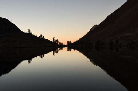 reflection of hills and trees in a mountain lake after sunset