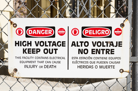 danger high voltage keep out sign on a chain link fence around electrical equipment Banco de Imagens