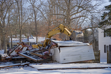 residential demolition with an excavator in the winter