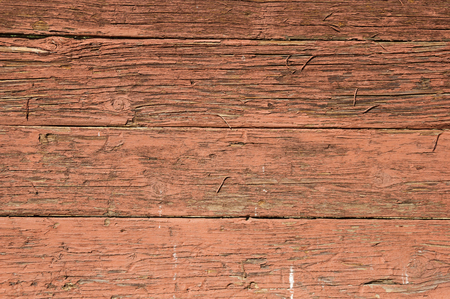 old red painted wood background with cracked and peeling paint