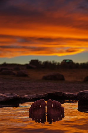 toes and feet poking out of a hot spring at sunset with reflection in the water and selective focus Stock Photo