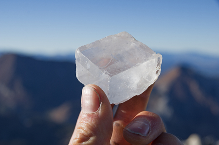a mans hand holding a calcite crystal on top of a mountain