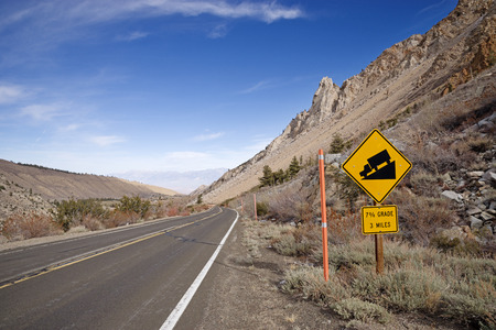 steep downhill with 7 percent grade sign on a mountain road Banco de Imagens - 94613055