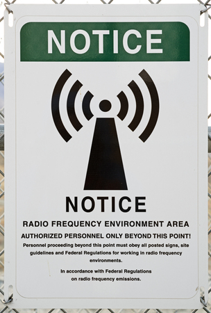 notice radio frequency environment warning sign on a chain link fence