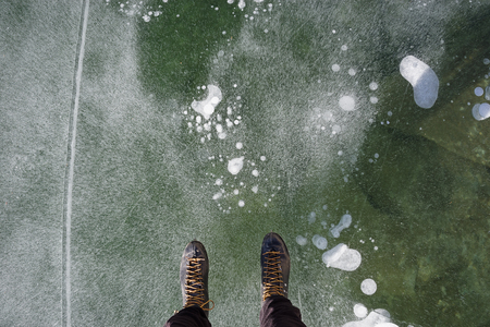 view down while ice skating on a lake showing the end of a mans legs and ice skates