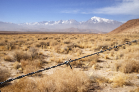 Barbed wire fence strand with dry fields and distant mountains with shallow depth of field Banco de Imagens - 96278260