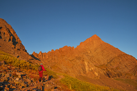 woman hiking up to Broken Hand Pass on the way to Crestone Needle Peak in the first light of the morning