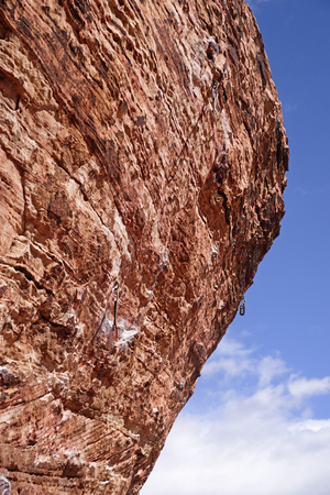 steep overhanging rock climb at Red Rock Conservation Area with quick draws hanging on bolts Banco de Imagens - 98303927