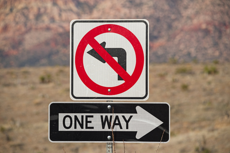 one way and no left turn signs in red black and white with out of focus mountains behind