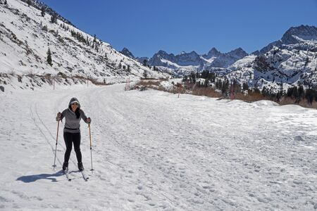a woman cross country skiing down a snow covered road in the mountains Stock fotó
