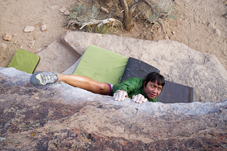 a woman bouldering on a traverse from above with a heel hook Banco de Imagens - 103235273