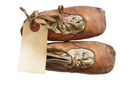 old worn baby shoes from 1908 with a blank paper tag tied onto the laces