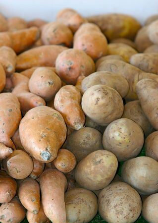 Two kinds of sweet potatoes stacked next to each other with foreground focus