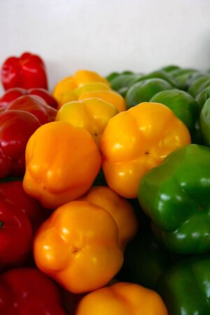 Red, yellow, and green peppers stacked next to each other next to white wall