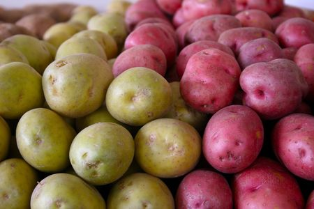 A large number of green and red potatoes stacked on a table beside each other Imagens