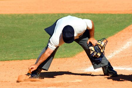 an umpire: Baseball umpire dusting off dirt from home plate with a brush with his mask in his other hand Stock Photo