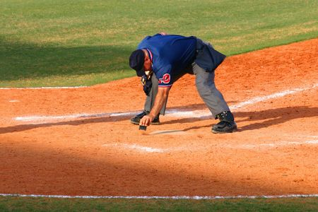 an umpire: Baseball umpire dusting off dirt from home plate with a brush in mid-afternoon