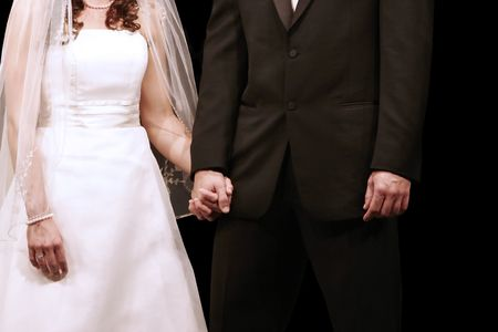 Bride and groom holding hands during their wedding ceremony with brides engagement ring showing photo