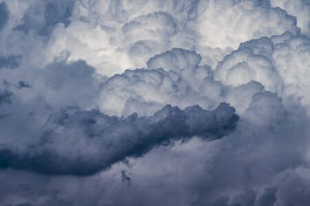 powerful and active white cumulonimbus cloud in a deep blue sky