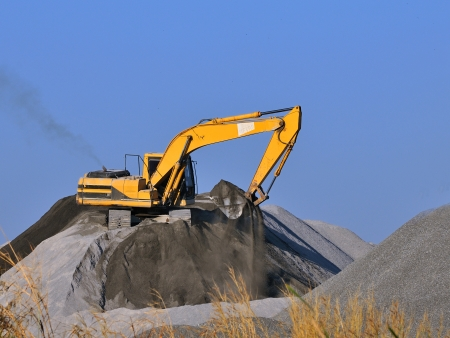Wheel loader Excavator unloading sand with water during earth moving works at construction site photo