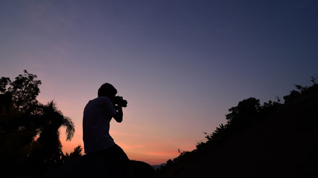 silhouette of man enjoying sunset photo