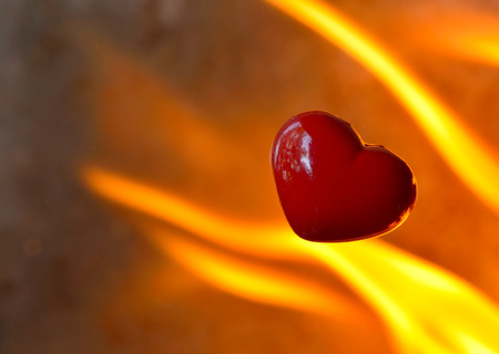 burning heart: burning heart with flames against fire background Stock Photo