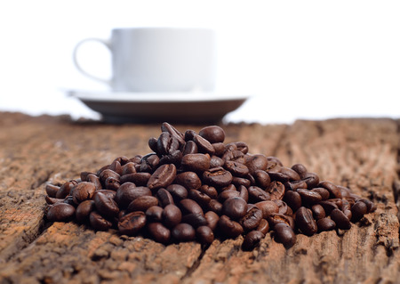 Closeup of coffee cup with roasted coffee beans on wooden background. View from top photo