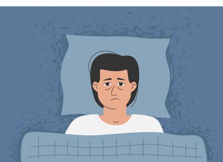 A man with wide eyes is lying in bed, he can't sleep. The problem with anxiety and insomnia.