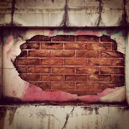 The crumbled surface of the wall revealing a brick structure inside Stock Photo