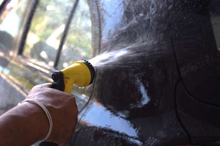sud: closed up the man use rubber tube to washing a car