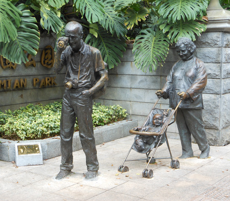 Happy family bronze statue. Mother wheeling baby carriage, father watching telescope.