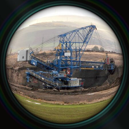 devastated land: Excavator in surface coal mine in objective lens