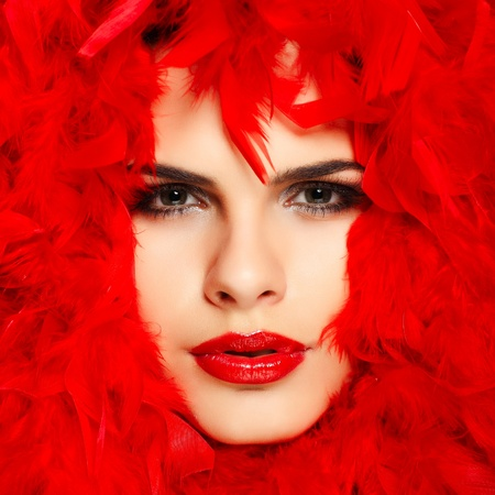 beautiful redheaded girl with red feathers Stock Photo