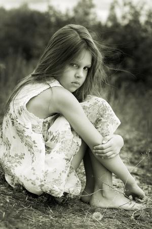 verdrietig meisje: Klein meisje een park vlakbij de rivier Stockfoto