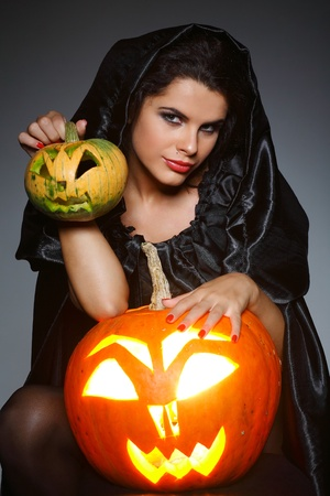 brunette in the suit of witch in night of Halloween