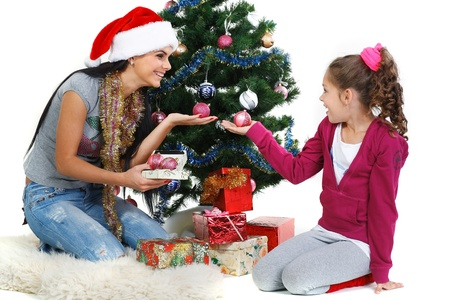 Mother and daughter near a christmas tree with gifts, isolated on a white background photo