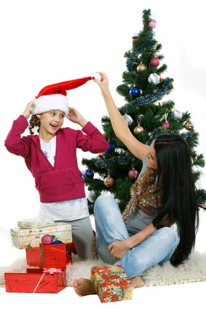 Mother and daughter near a christmas tree with gifts, isolated on a white background Stock Photo - 10805219